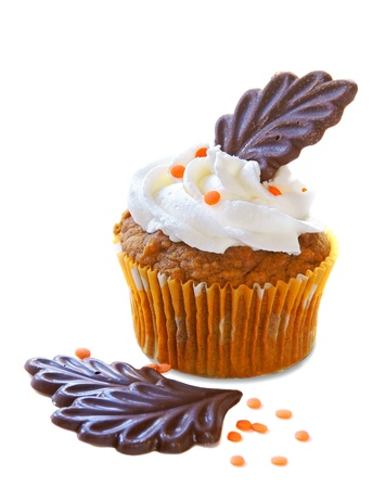 Autumn decorated cupcake with chocolate leaves and orange sprinkles                   Stock Photo