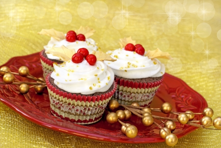 Chocolate cupcakes with vanilla icing decorated with gold colored fondant leaves and red candy.                  photo
