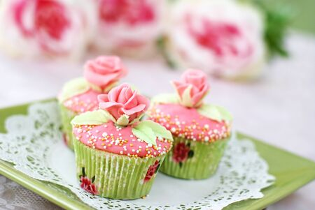 Vanilla cupcakes with pink frosting decorated with pearls and roses made of fondant                   Stock Photo