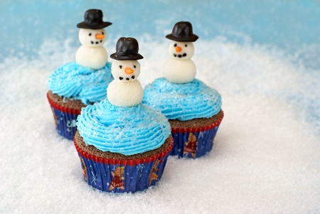 Chocolate cupcakes with vanilla frosting decorated with snowmen made of fondant and rolled in sugar.
