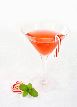 Christmas cocktail decorated with candy canes and a mint leaf.