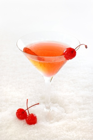 Cherry cocktail in a martini glass decorated with maraschino cherries, on snow.                    Stock Photo
