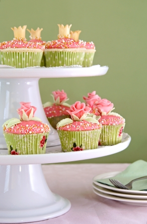 Vanilla cupcakes with pink frosting decorated with roses and crowns made of fondant.