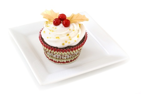 Chocolate cupcake with vanilla frosting decorated Holly made of with gold fondant leaves and red candy