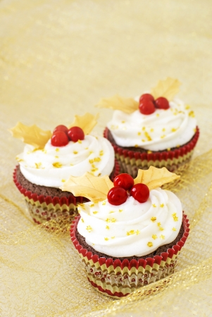 Chocolate cupcakes with vanilla icing and red candy berries and gold fondant leaves