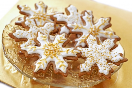 Snowflake gingerbread cookies decorated with icing, gold, and pearls.