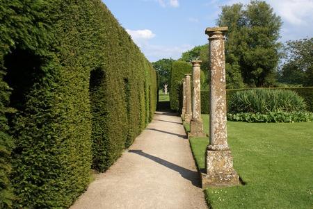 elizabethan: garden pathway with Elizabethan columns and sculptured hedge
