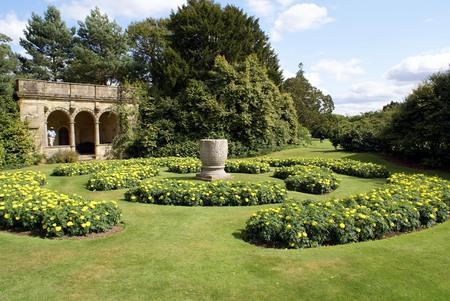 summerhouse: summerhouse urn and flower beds in a garden