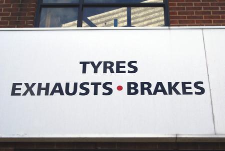 frenos: Los neumáticos, tubos de escape y frenos firman. garaje. taller de carrocería de automóviles o vehículos