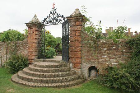 garden gate: ornate wrought iron garden gate with a unicorn sculpture Stock Photo
