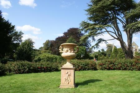 vintage sculptural urn or vase on a pedestal in a garden Stock Photo