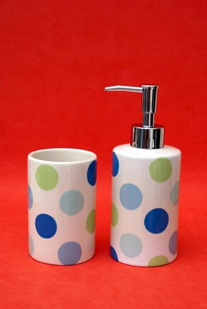handwash: bottle of liquid soap and cup. bathroom toiletry