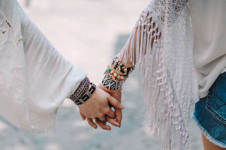 Hands of two young girls wearing hippy clothes with bracelets. Contemporary bohemian style. Spirit of freedom. Fashion shot. Фото со стока