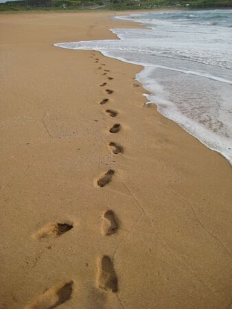 footprints in sand with wave on deserted beach   Stock Photo