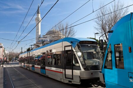 A high-speed new tram on an Istanbul street in the background of a mosque.