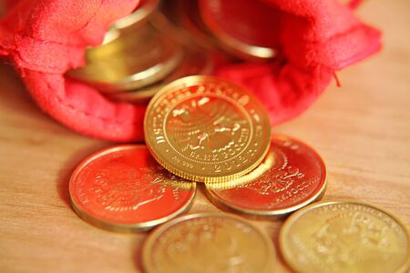 Red bag with gold coins on the table