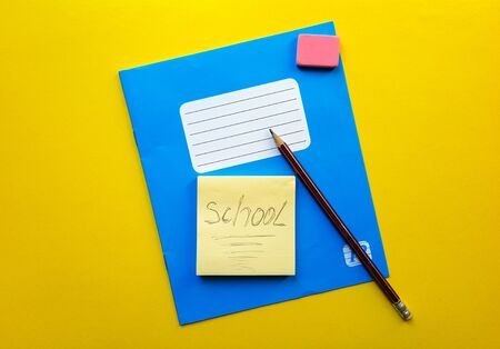 Blue notebook and textbook copy butt for school subjects, eraser, pencil, paper clip on a yellow background. The word school is written in pencil. Flat lay, copy space, top view, place for text