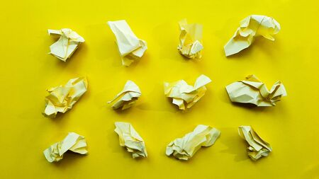 Ball crumpled paper ball isolated on a yellow background. Crumpled paper for texture. Crumpled paper after a brainstorming was thrown into the bin. A piece of yellow crumpled paper on a yellow background.