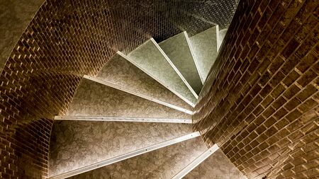 top view of a narrow stone spiral staircase lined with ceramic brown tiles.