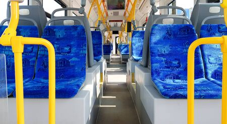 Ukraine, Kiev - September 08, 2019: Empty city tram salon. Public ground transportation within the city. Seats for passengers. Handrails for carrying out. Contactless payments of transport validators. Passenger city transport. Редакционное
