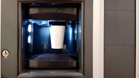 White paper cup in the window of a vending coffee machine. The process of making coffee in a wading machine.