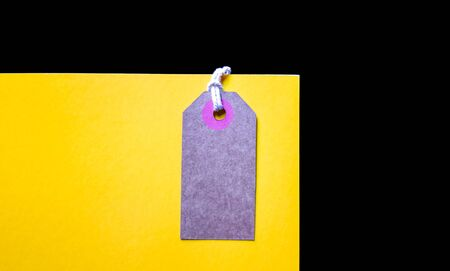 Blank brown cardboard price tag or label on yellow background. top view.