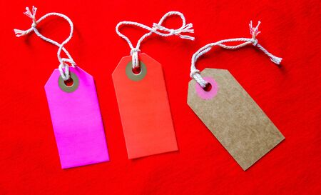 three colored tags on a white rope, red background.