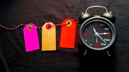 On a black background, blank colored labels lie on a rope. On the side is a small black alarm clock. Beautiful photo with place for an inscription, mock up