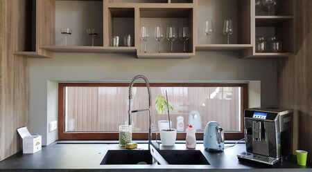 Ukraine, Kiev - September 24, 2019: Modern kitchen with brown wooden furniture, stone countertops, sink and faucet. A coffee machine is on the table. Interior, kitchen design in a big house. Kitchen worktop and kitchen area Redakční