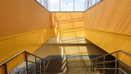 light rail station. Design of a bus stop and a pedestrian underpass with steps and railings made of yellow panels and a glass roof