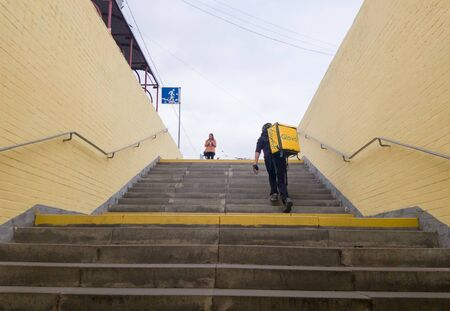 Ukraine, Kiev - September 26, 2019: A walking Glovo courier service provider with a yellow backpack rises the steps of the transition, hurries to deliver the order on time to the customer. Redakční