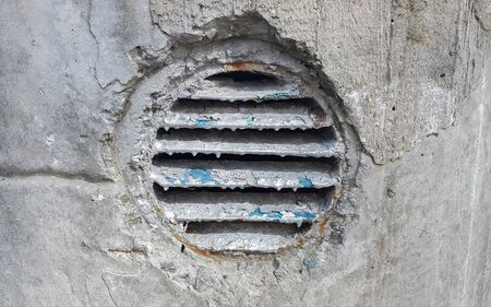 ventilation hole in concrete. Metal industrial round ventilation cover. Rusty and dirty old round ventilation frame with horizontal metal stripes
