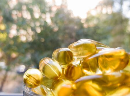 Fish oil capsules in a transparent plate. A lot of vitamin omega-3 against the background of nature and the park. Close up, high resolution product. Metabolism in the body. The body of calcium. A quick way to lose weight.