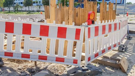 Plastic Protective barrier fences the site of road work. Red and white plastic fence near the street repair site. Construction work on the street, road repair, protective fence.
