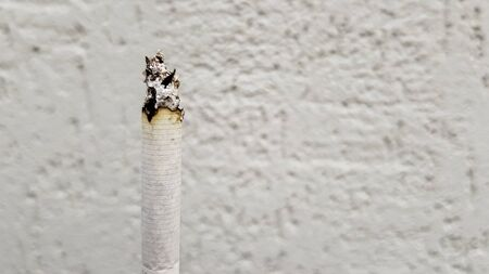 Secondhand smoke concept. On a tobacco-free day, smoking is undesirable for society. Vertical cigarette smoking on a white wall background with copy space. Text no to cigarettes
