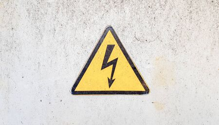 Danger sign of high voltage electricity. Yellow triangular sign with a lightning in the center. This warning is written on an old metal surface painted with gray paint 免版税图像