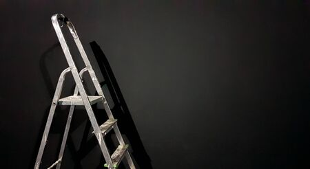 Iron step ladder against a gray wall. Preparing for home repairs. Old and dirty aluminum in an empty room, shadow. White gray stucco concrete wall copy space background with staircase. 3D rendering.