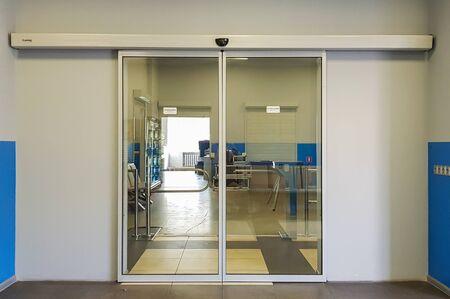 Puerta frontal de vidrio corrediza vacía en el aeropuerto. Puertas de cristal en la oficina. Entrada de cristal. Entrada al edificio de administración equipado con puerta automática. Foto de archivo