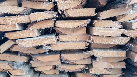old wooden boards piled on a stack close-up. wood texture. A pile of boards stacked on top of each other. Lumber for use in construction. Isolated boards. The side surface of the board background