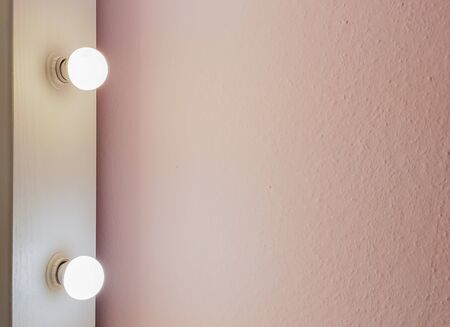 Modern new flat pink wall with two light bulbs from a large floor mirror for makeup and full-length shopping. Abstract modern trendy texture background. Copy space for your text