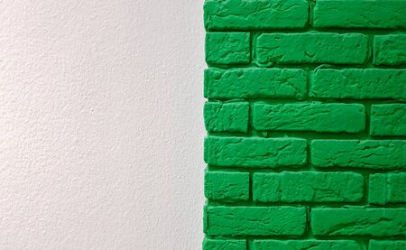 Modern new flat pink wall with a decorative brick column painted green. Abstract modern trendy texture background. Copy space empty space for your text and advertisement