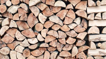 A neatly folded log of chopped wood. The fire is melting. Firewood stacked on top of each other. Firewood is collected for heating in cold weather. Background texture of stacked dry firewoods.
