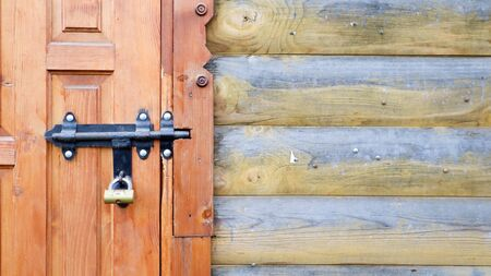 Old wooden door with a black metal bolt. Close up view of a lock and latch on a wooden door. Rustic wooden metal door latch. This sliding lock can be used on awnings, on desktops or on fences.