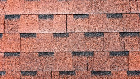 Close up view on Asphalt Roofing Red Shingles Background. Roof Bitumen Shingles - Roofing Construction, Roofing Repair. Red Shingles on the Roof of the House. Background of Red Shingles.