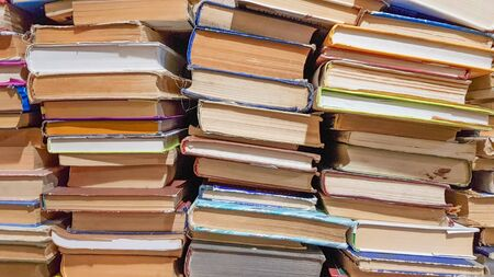Many used old books in the school library. chaotic layout of stacks of literature, selective focus. A pile of books ends with stacked background. books in a library - backdrop.