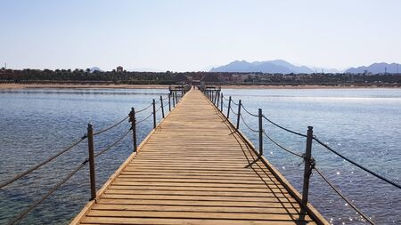 Long pontoon on the Red Sea in Egypt. Pontoon for descent into the water. Wooden bridge on the territory of the Amway Hotel in Sharm El Sheikh with metal fences and a rope over the sea with waves.