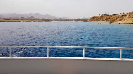 beautiful view from the deck of a cruise ship in the Red Sea in Egypt. Egyptian rocky coast landscape with a yacht. Part of the ship against the backdrop of the desert and the sea