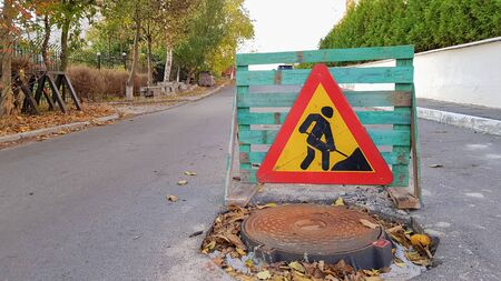 Road repair. Sewer manhole on the roadway. Triangular warning car drivers sign with a man with a yellow spade with red. Men at work. Traffic signs, travel restrictions