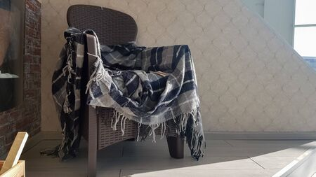 A modern wicker plastic chair with a plaid plaid in a house or apartment. The concept of home comfort and tranquility. Close-up of a chair with a plaid wicker on the veranda with side Imagens