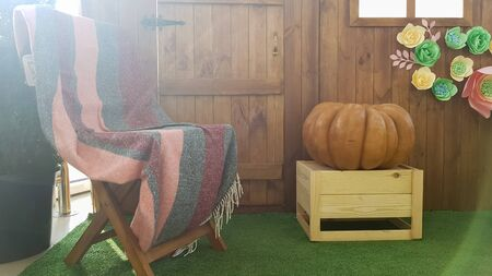 beautiful autumn landscape with one pumpkin and a wooden vintage chair with a plaid on a terrace near a wooden small house Imagens